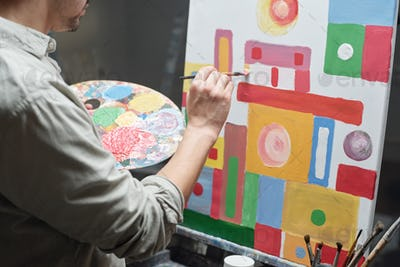 Young male artist with color palette and paintbrush working over painting