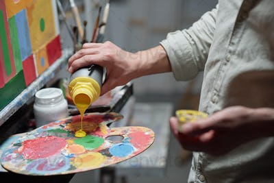 Hand of young painter adding yellow color on palette before start painting
