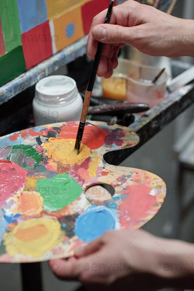 Hand of young professional painter mixing colors on palette in front of easel