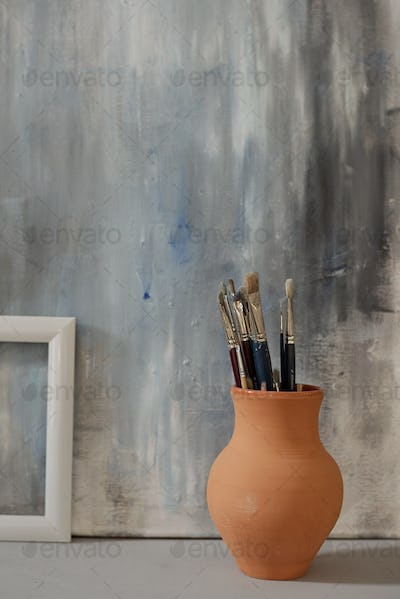 Brown clay jug with group of paintbrushes standing on the floor against painting
