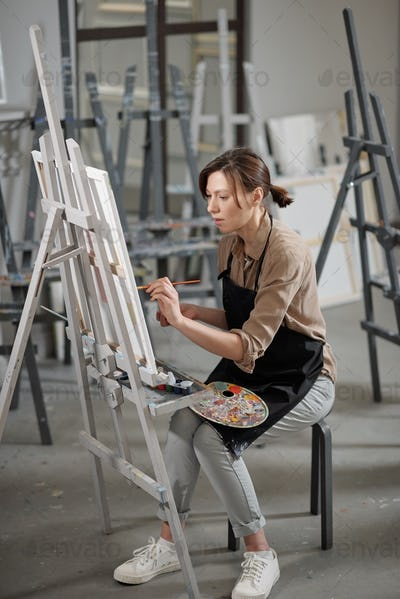 Young diligent student of painting course sitting on chair in front of easel