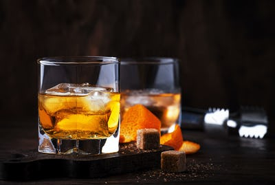 Alcoholic old fashioned cocktail with orange slice, cherry and orange peel garnish