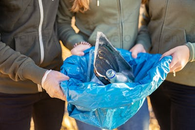 Midsection of young volunteers holding garbage bag