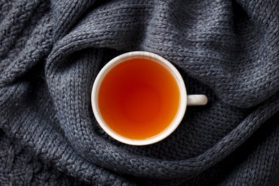 Cup of Tea. Grey Knitted Scarf Background. Top View.