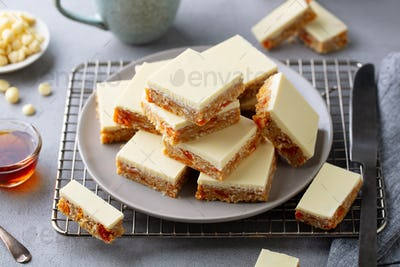 Oat, Coconut, Apricot Bars with White Chocolate on a Plate. Grey Background. Close up.