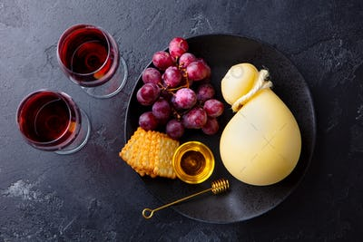 Caciocavallo Cheese with Grapes, Crackers and Red Wine. Dark Background. Top view.