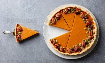 Pumpkin pie on a plate. Grey background. Close up. Top view.