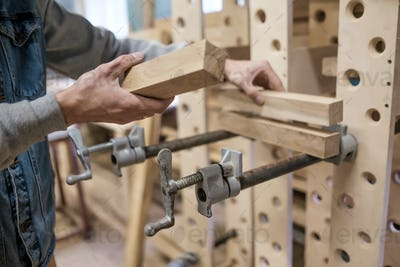 Man gluing furniture details in the carpentry workspace.