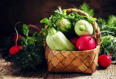 Wicker basket with a crop of spring vegetables and herbs