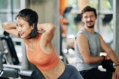 Woman exercising in hyperextension machine