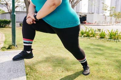 Stretching overweight sportswoman