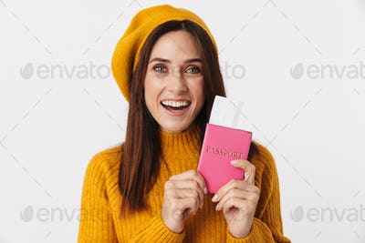 Image of beautiful adult woman smiling and holding travel tickets