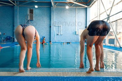 Male and female swimmers on start, back view