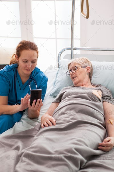 Female doctor helping old woman sitting on bed