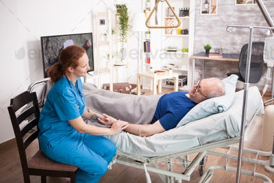 Female doctor holding senior man laying on bed