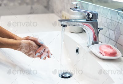 Woman is washing hands with soap. Coronavirus pandemic. Covid-19