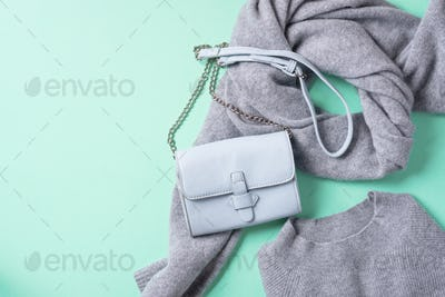 Fashion concept flat lay. Winter warm clothes flat lay on blue background. Wool feminine clothes