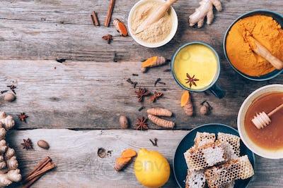 Ingredients for turmeric latte. Turmeric powder, curcuma root, cinnamon, ginger over wooden