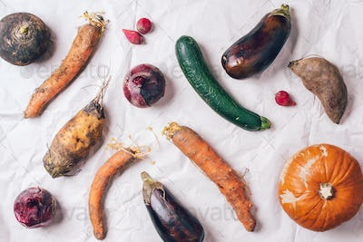 Ugly organic rotten vegetables with mutations on craft paper background. Concept of zero waste
