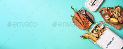 Peeled vegetables in white compost bin on blue background. Trash bin for composting with leftover