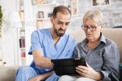 Health visitor helping senior woman to use tablet