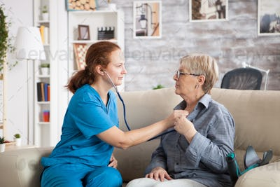 Health visitor and a senior woman in nursing home sitting on couch