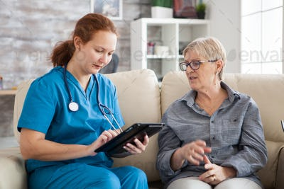 Senior woman and female nurse with tablet sitting on couch