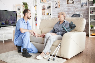 Joyful old woman in a nursing home talking with her health visitor