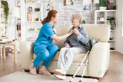 Female nurse sitting on couch with old woman