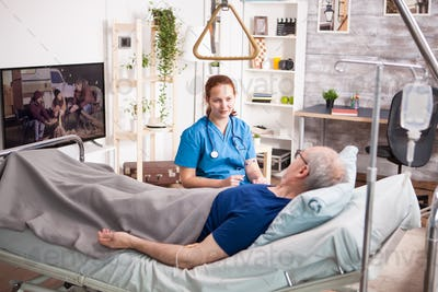 Female doctor with stethoscope sharing comfort to old man