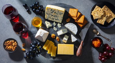 Cheese Assortment on Dark Marble Cutting Board with Red Wine. Grey Background. Top view.