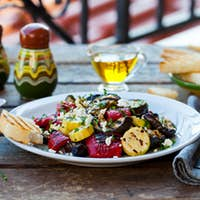 Grilled Vegetables Salad with Feta Cheese in White Plate on Wooden Table. Outdoor Background.