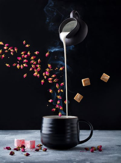 Rose Flower Tea with Milk, Flying Ingredients. Black Background.