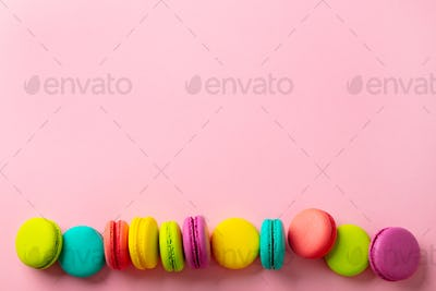Macaroons dessert on pink background. Copy space. Top view.
