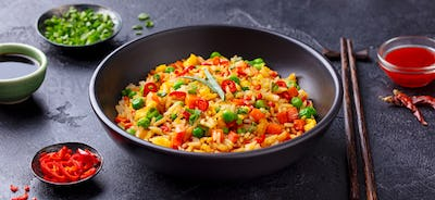 Asian fried rice with egg and vegetables. Dark stone background. Close up.