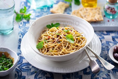 Spaghetti pasta with olives, fresh herbs sauce in a white bowl. Blue textile background.