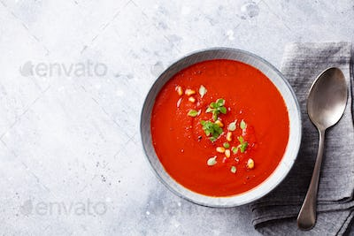 Tomato soup with fresh herbs and pine nuts in a bowl. Grey stone background. Copy space. Top view.