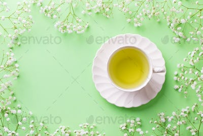 Green tea in a white cup with gypsophila flowers on green pastel background. Top view. Copy space.