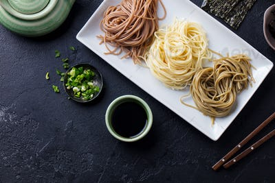 Assortment of Japanese Soba Noodles with Sauce and Garnishes. Black Slate Background. Top view.