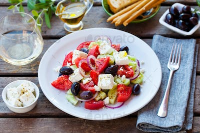 Greek salad. Fresh vegetables, feta cheese and black olives with white wine. Close up.