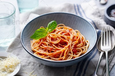 Pasta, Spaghetti with Tomato Sauce and Fresh Basil in a bowl. Grey Background. Close up.