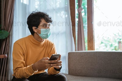 man wearing medical masks using mobile phone during virus epidemic lockdown