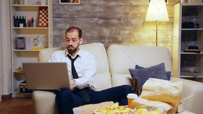 Businessman reaching out for his beer while working on laptop