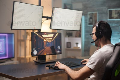 Young man with eyeglasses relaxing playing shooter games