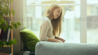 Little girl sitting near by window with tablet, remote studying, being at home