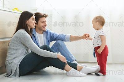 Parents teaching baby son to walk, sitting on kitchen floor