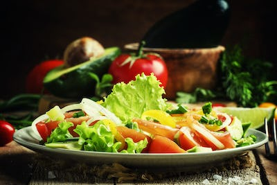 Salad with avocado, salmon, lettuce, onions and peppers on a plate