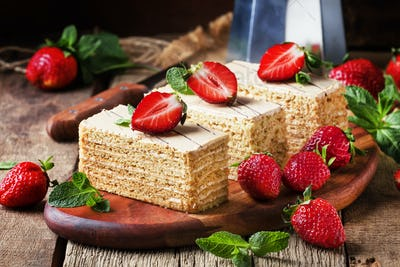 Traditional russian honey cake decorated with strawberries and green mint