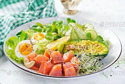 Salt salmon salad with greens, cucumbers, eggs and avocado.