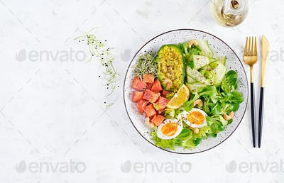 Salt salmon salad with greens, cucumbers, eggs and avocado